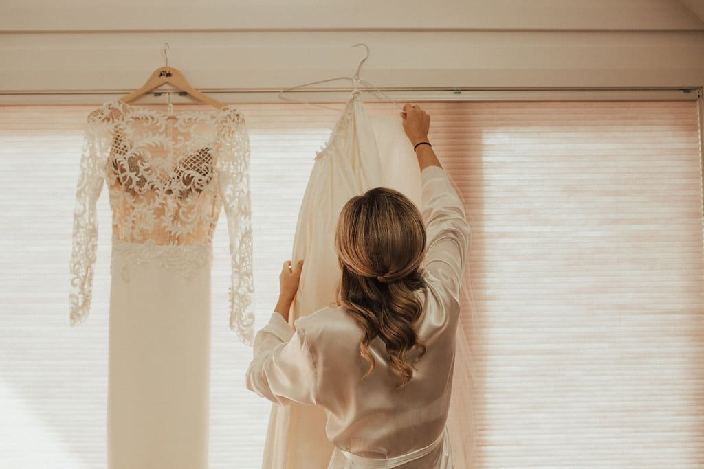 Real Weddings | Vinka Design | Real Brides Wearing Vinka Gowns | Olivia and Ben - beautiful wedding dress hanging showing detail of bodice with nude base and lace detail