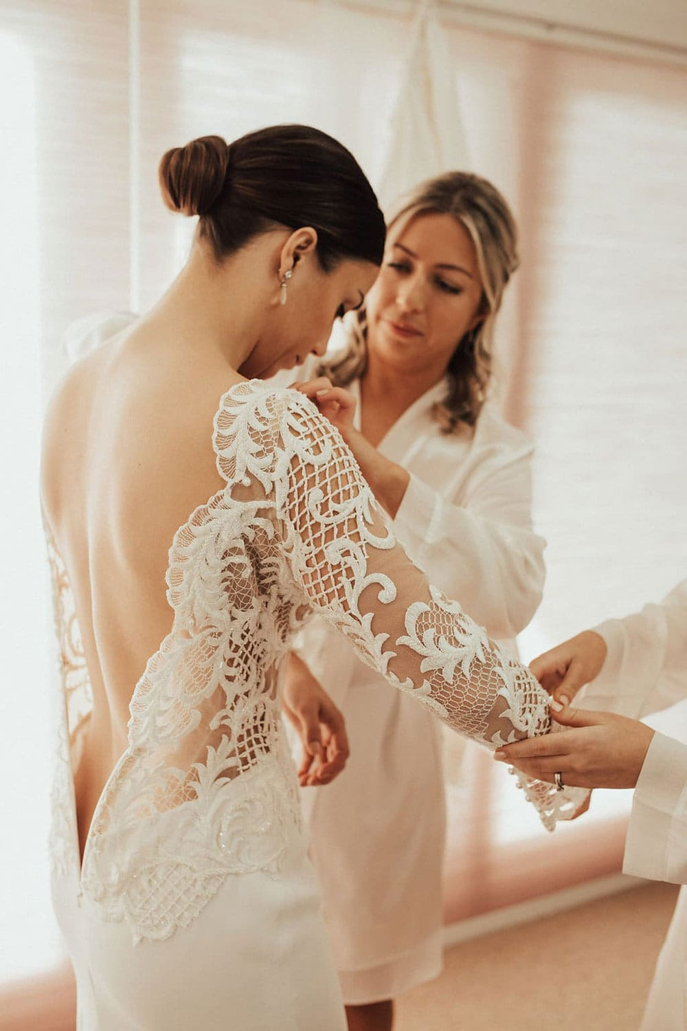 Real Weddings | Vinka Design | Real Brides Wearing Vinka Gowns | Olivia and Ben - Olivia getting ready, beautiful detail of bodice with nude base and lace detail and low back