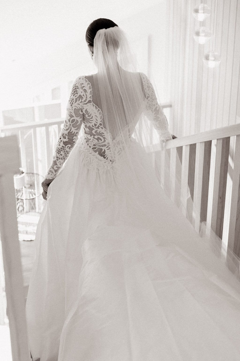 Real Weddings | Vinka Design | Real Brides Wearing Vinka Gowns | Olivia and Ben - Olivia walking down stairs with dramatic silk train flowing behind her in black and white