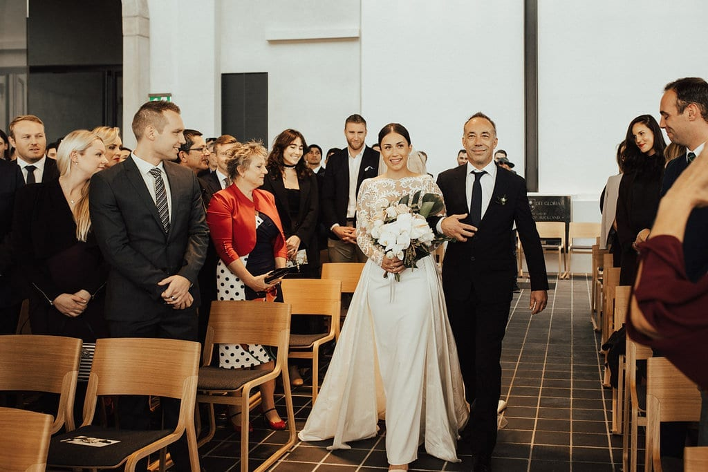 Real Weddings | Vinka Design | Real Brides Wearing Vinka Gowns | Olivia and Ben - Olivia being walked down the aisle at wedding ceremony at Bishop Selwyn Chapel