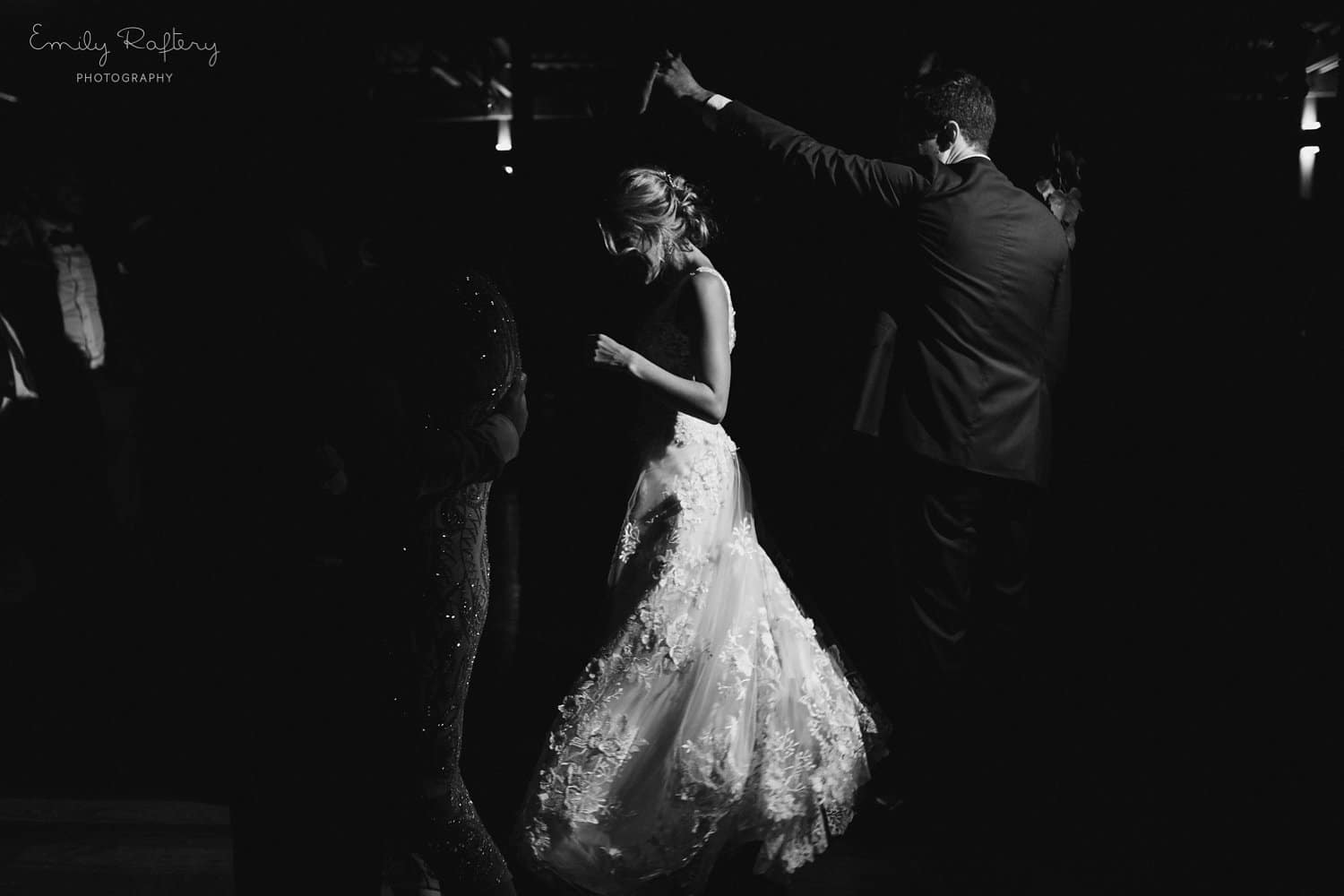 Real Weddings | Vinka Design | Real Brides Wearing Vinka Gowns | Helena and Tim dancing at reception in dim light with beautiful bespoke white dress with lace detail flowing and shining in b
