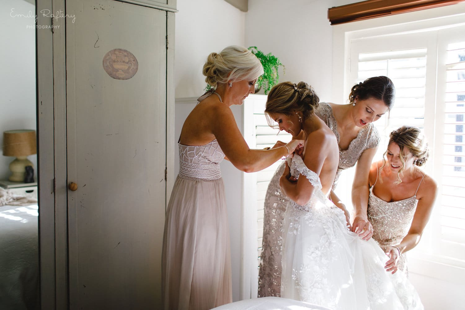 Real Weddings | Vinka Design | Real Brides Wearing Vinka Gowns | Helena and Tim - Helena with bridesmaids helping her into beautiful bespoke Delta wedding dress