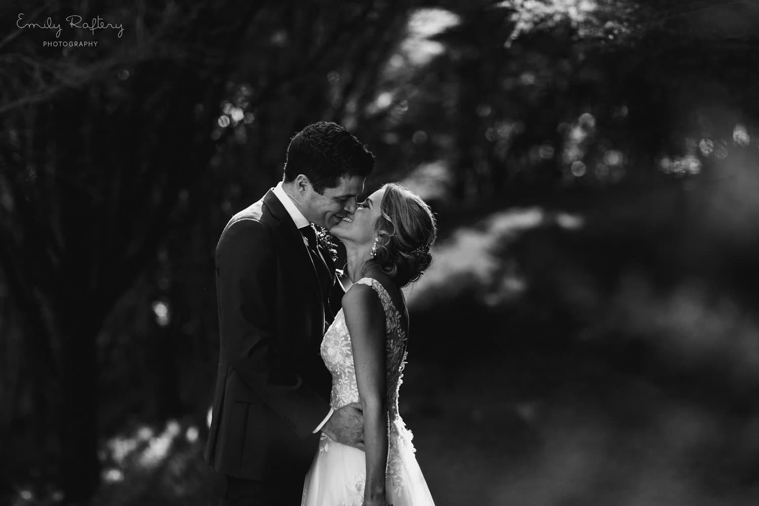 Real Weddings | Vinka Design | Real Brides Wearing Vinka Gowns | Helena and Tim black and white kissing photo at Kauri Bay Boomrock