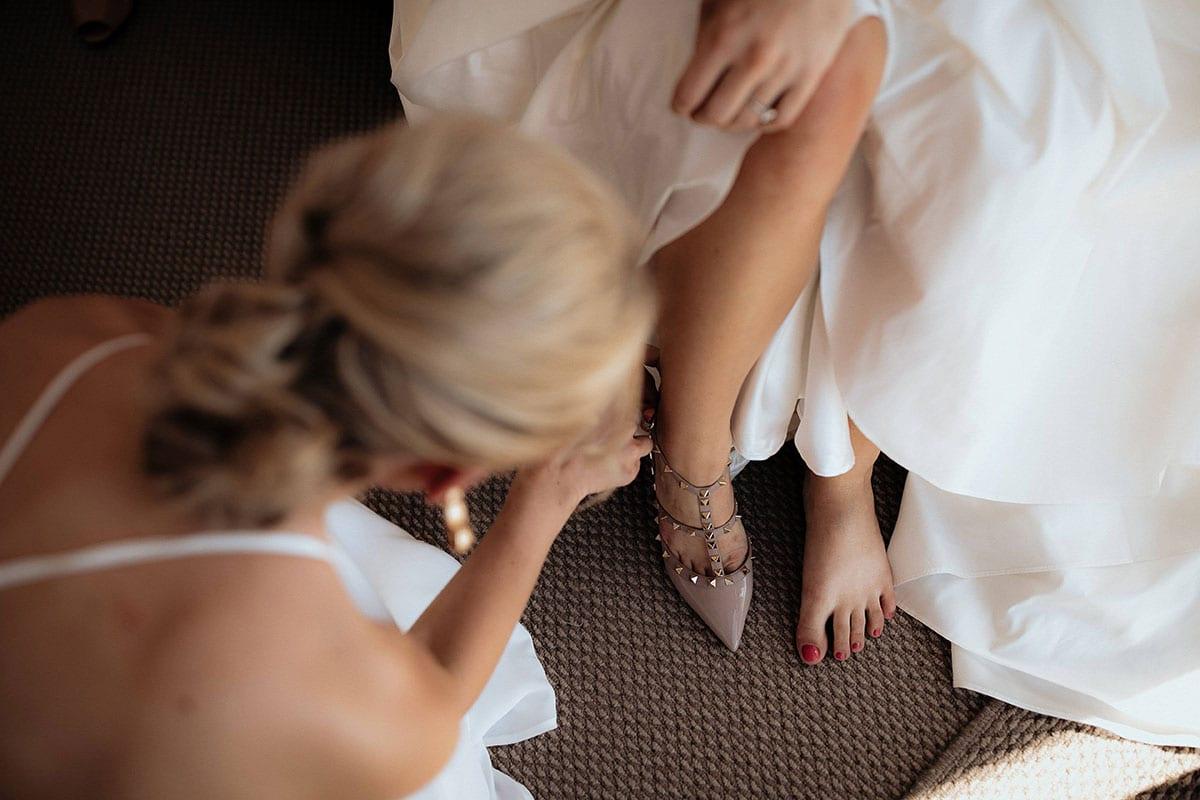 Real Weddings | Vinka Design | Real Brides Wearing Vinka Gowns | Lauren and Martyn - Lauren puttin on shoes