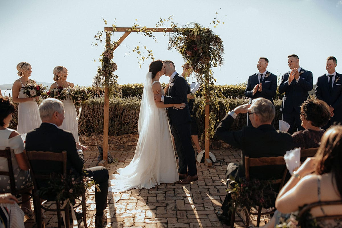 Real Weddings | Vinka Design | Real Brides Wearing Vinka Gowns | Lauren and Martyn kissing in arch at wedding ceremony