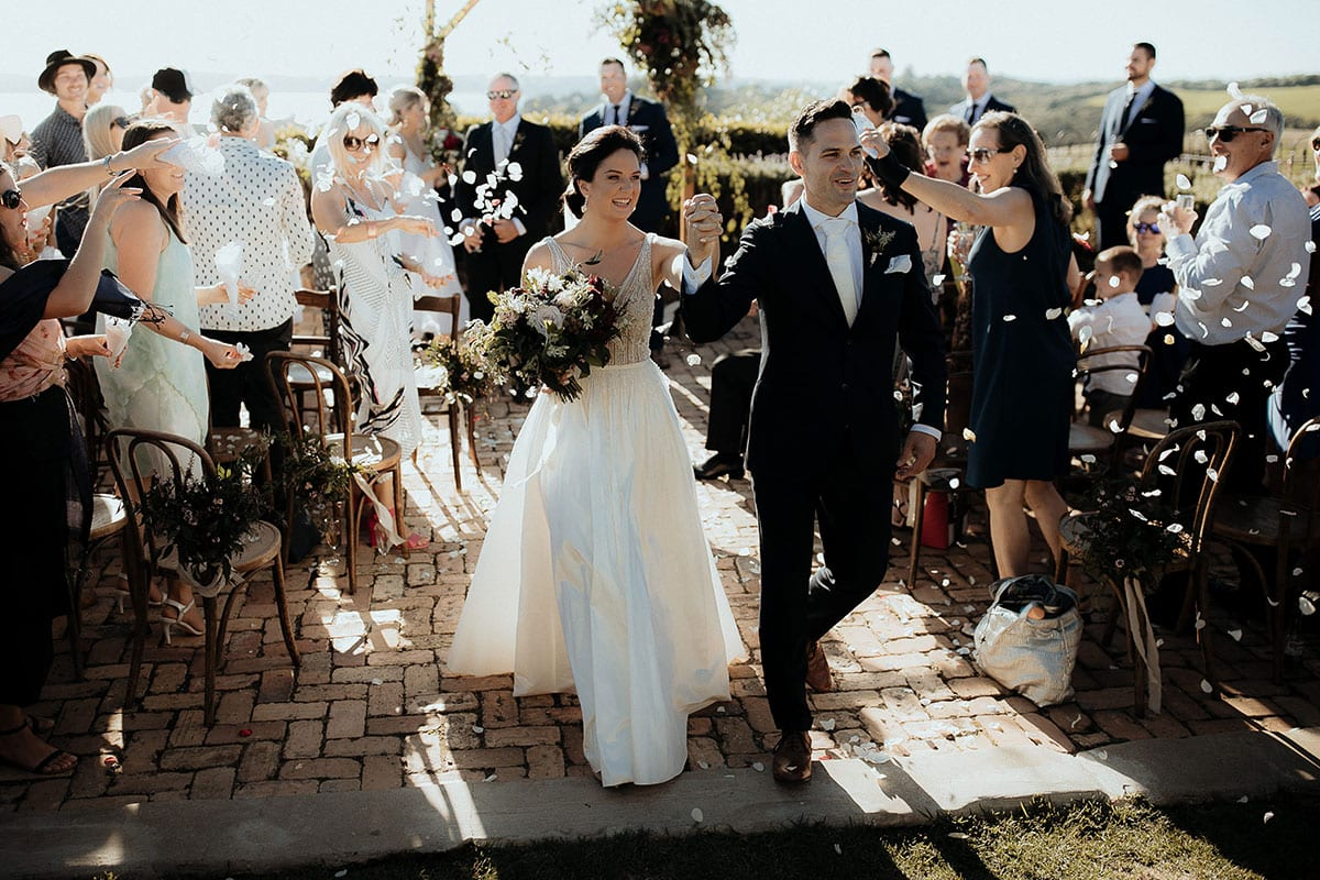 Real Weddings | Vinka Design | Real Brides Wearing Vinka Gowns | Lauren and Martyn just married walking down aisle with confetti
