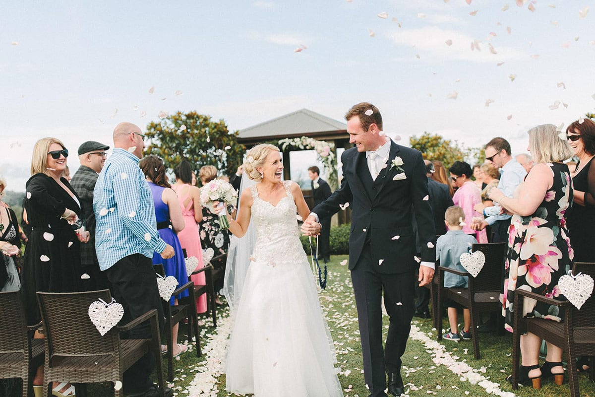 Real Weddings | Vinka Design | Real Brides Wearing Vinka Gowns | Louise and Ryan walking down aisle with confetti