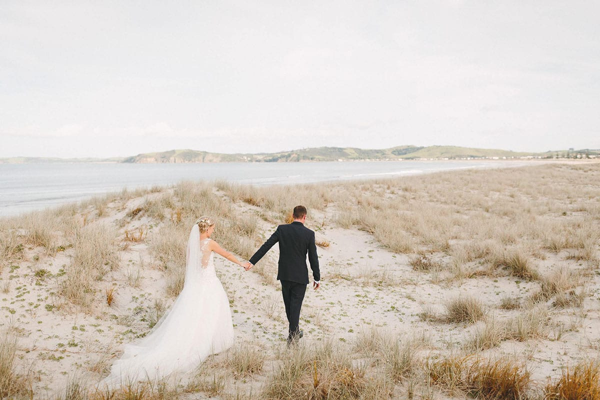 Real Weddings | Vinka Design | Real Brides Wearing Vinka Gowns | Louise and Ryan walking away over the sand dunes with dress train flowing