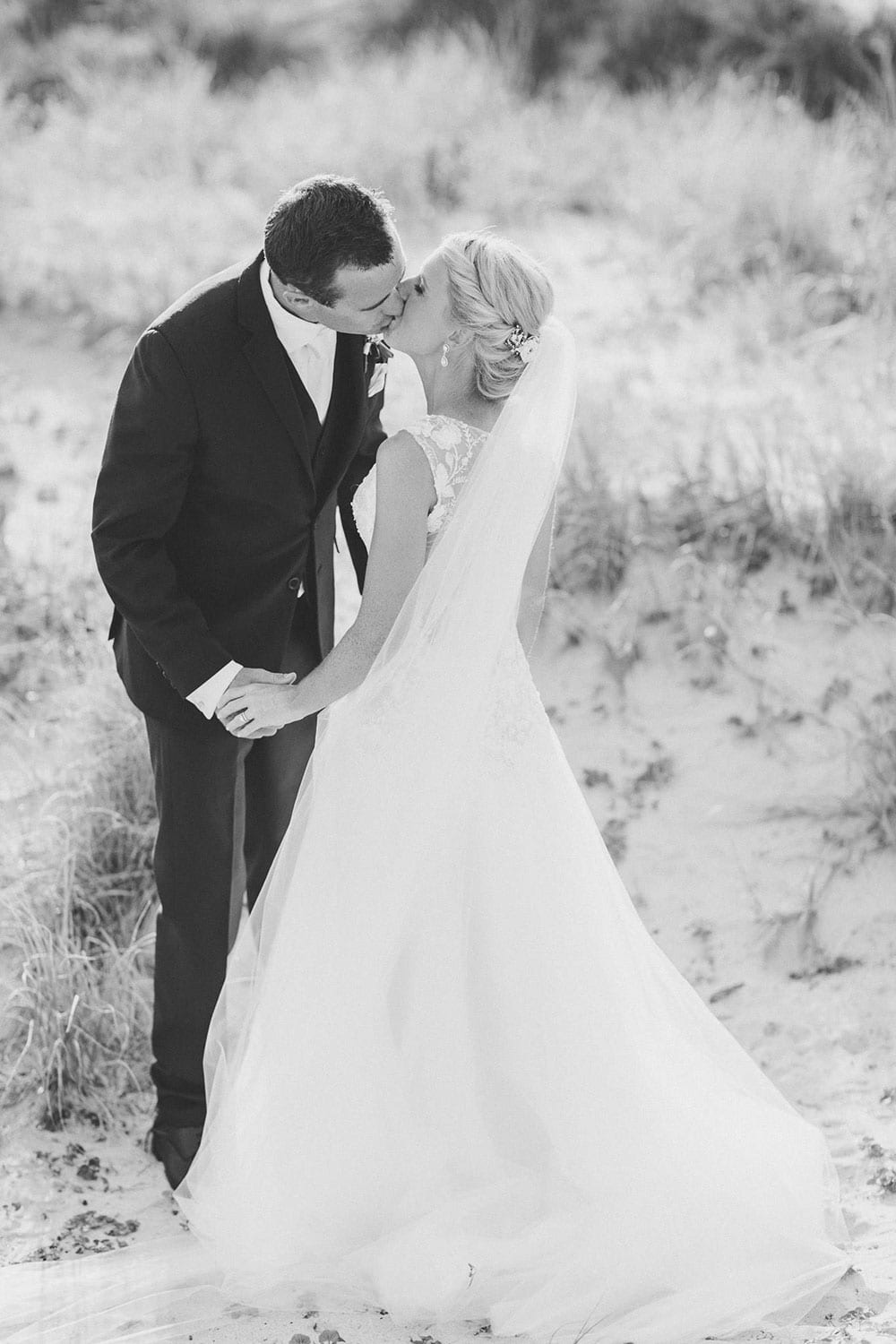 Real Weddings | Vinka Design | Real Brides Wearing Vinka Gowns | Louise and Ryan kissing on the sand dunes in black and white