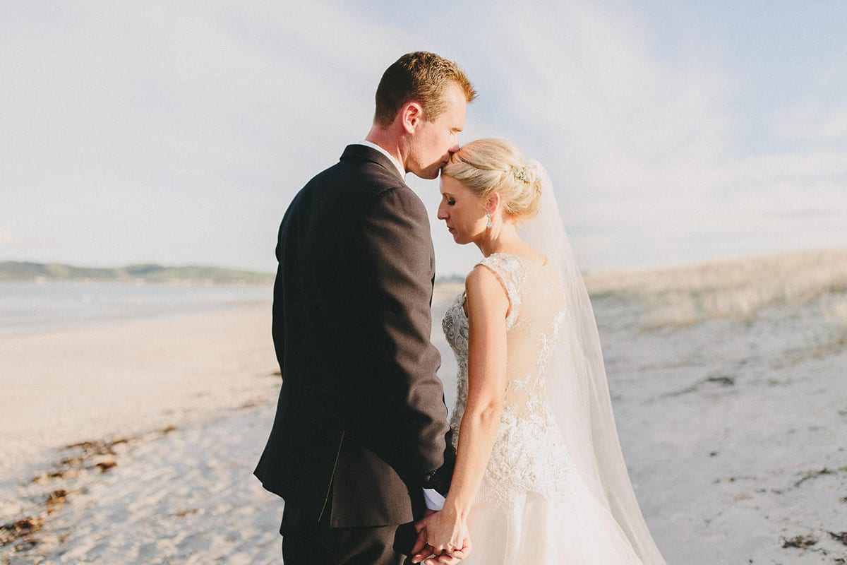 Real Weddings | Vinka Design | Real Brides Wearing Vinka Gowns | Louise and Ryan facing each other and Ryan kissing her head on the beach