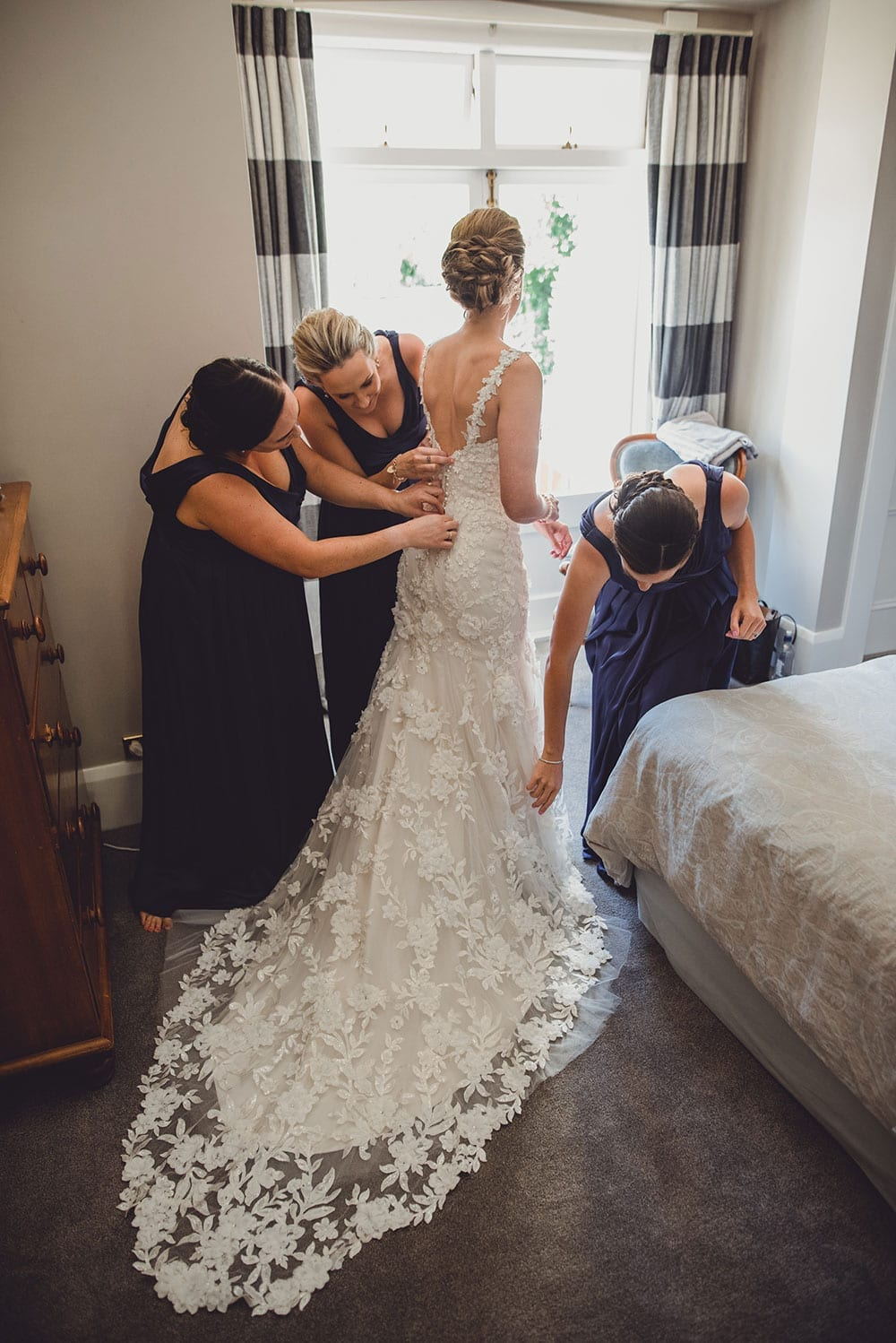 Real Weddings | Vinka Design | Real Brides Wearing Vinka Gowns | Claire and Paul - Claire being dressed with train flowing and lace detail showing