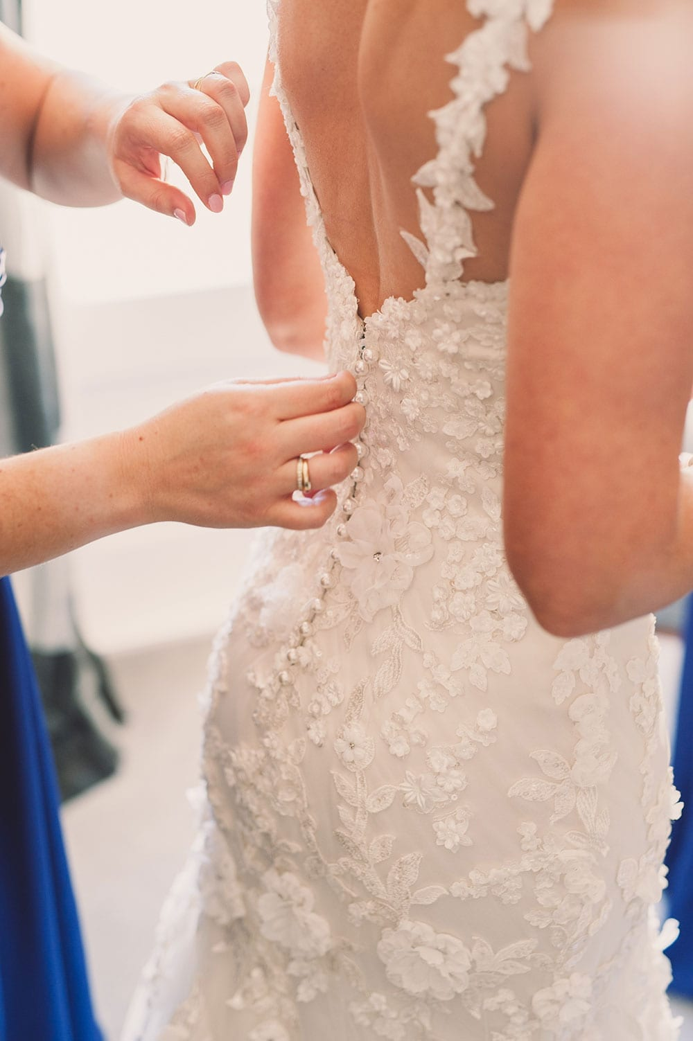 Real Weddings | Vinka Design | Real Brides Wearing Vinka Gowns | Claire and Paul - Claire being dressed with detail buttons being fastened