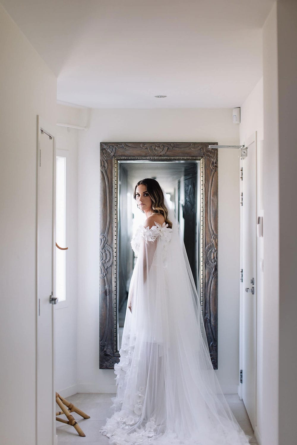Real Weddings | Vinka Design | Real Brides Wearing Vinka Gowns | Candice and Michael - Candice in hallway with mirror back of bespoke dress detail and train displayed