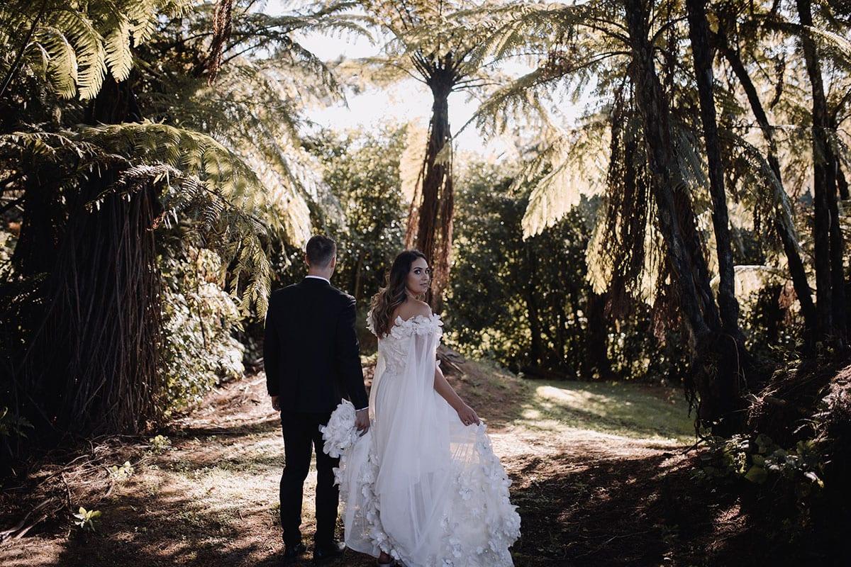 Real Weddings | Vinka Design | Real Brides Wearing Vinka Gowns | Candice and Michael walking away through Ataahua Gardens Venue in Tauranga
