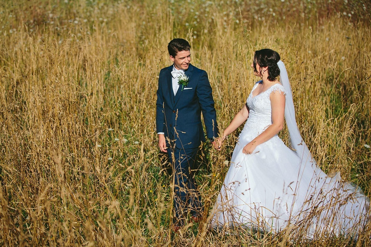 Real Weddings | Vinka Design | Real Brides Wearing Vinka Gowns | Bespoke gown with beaded lace bodice and tulle skirt | Kat and Logan walking through field