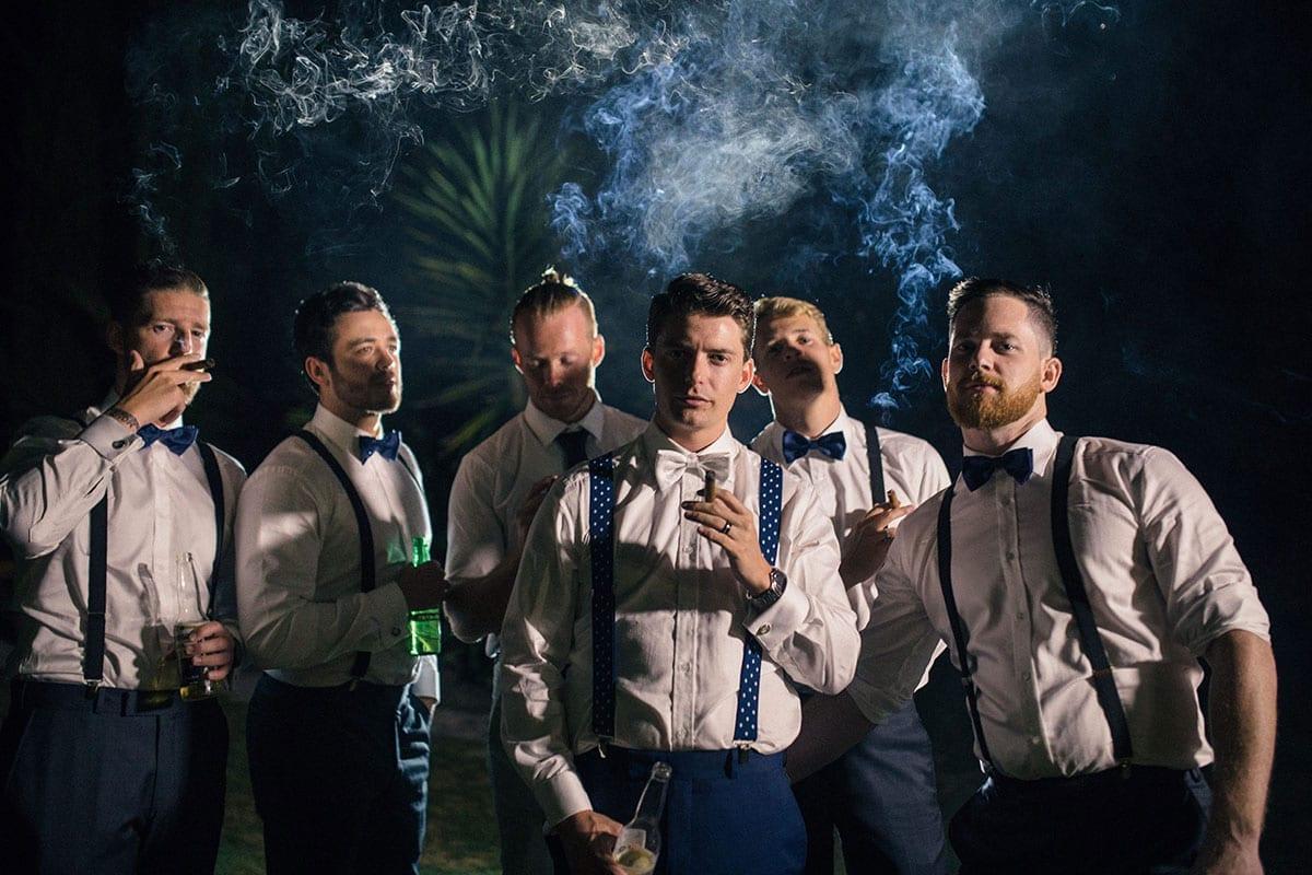 Real Weddings | Vinka Design | Real Brides Wearing Vinka Gowns | Kat and Logan - Logan smoking cigar with groomsmen