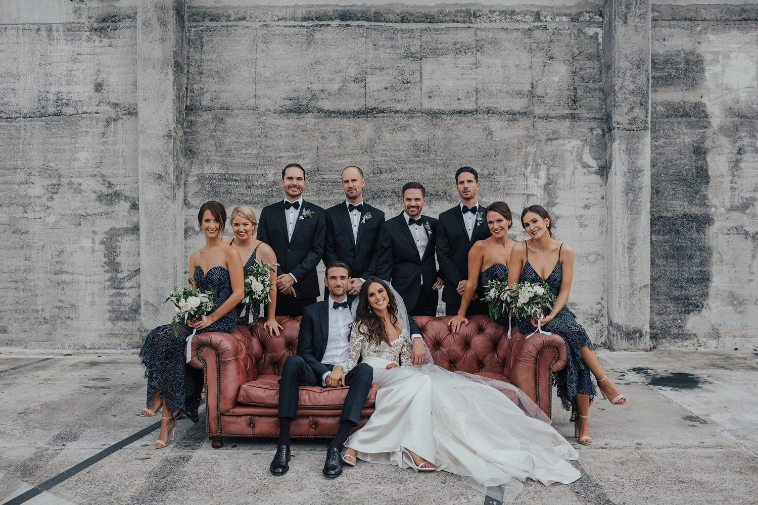Real Weddings | Vinka Design | Real Brides Wearing Vinka Gowns | Hannah and Campbell with bridal party posing around a sofa