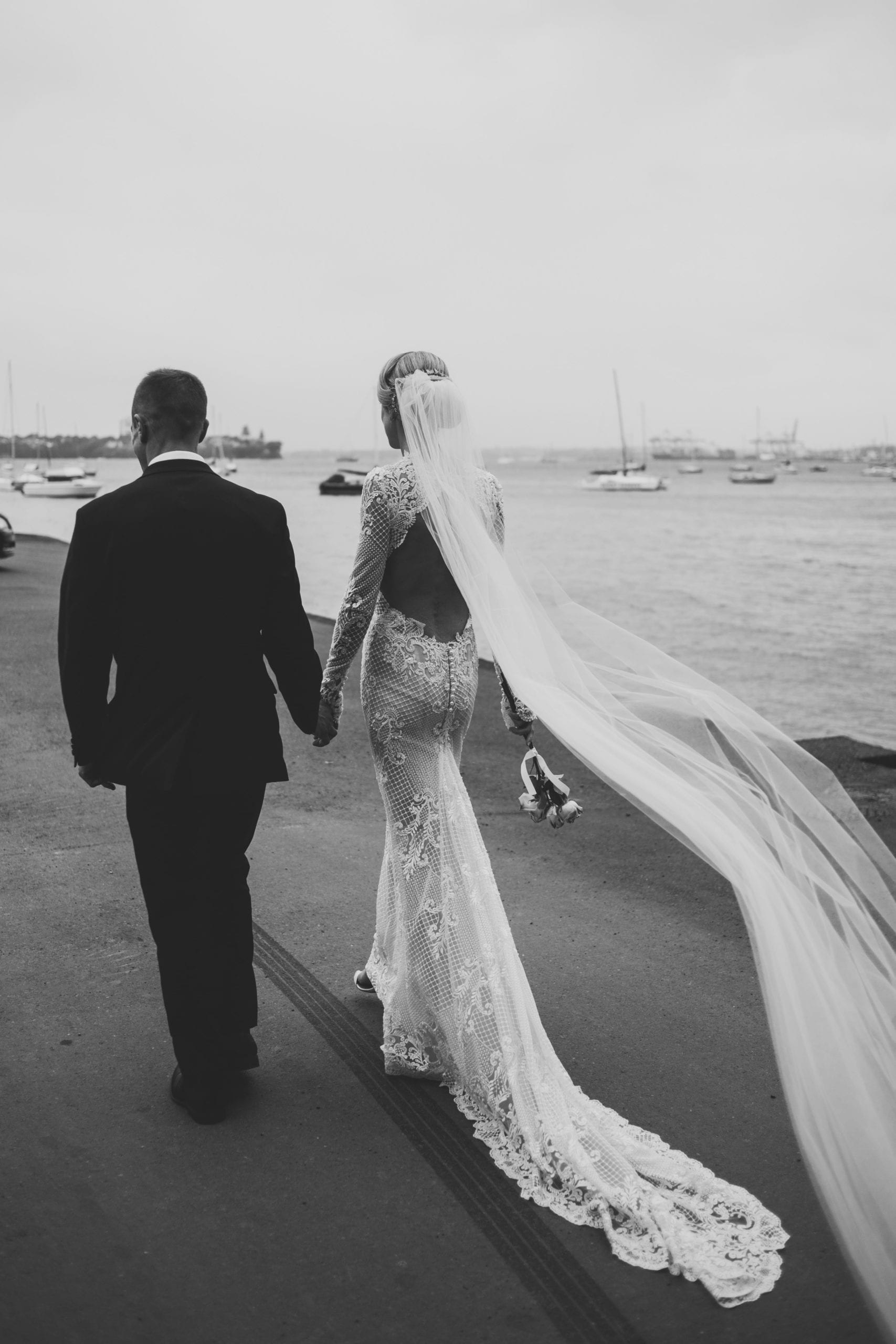 Real Weddings | Vinka Design | Real Brides Wearing Vinka Gowns | Hayley and Tonchi walking away next to the sea in black and white