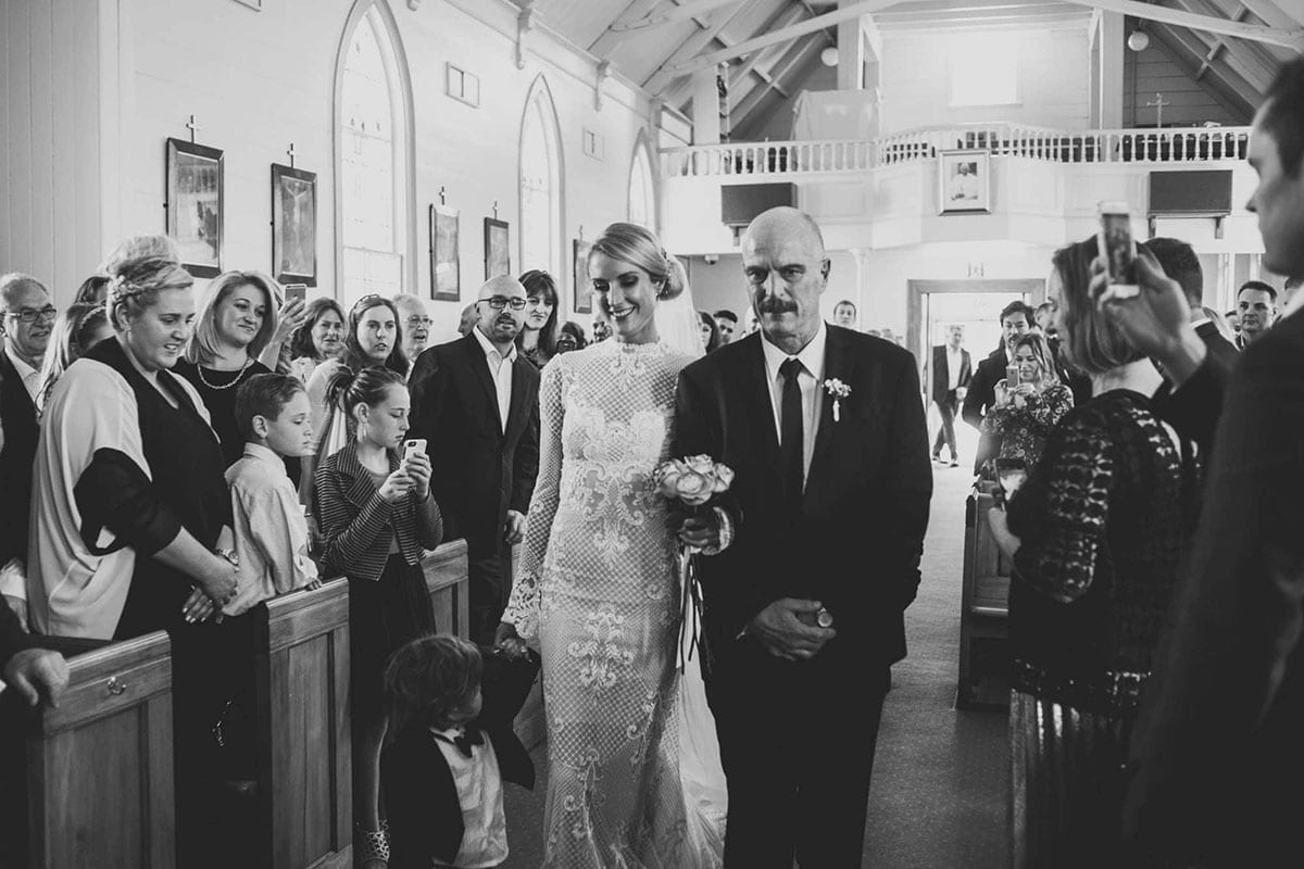 Real Weddings | Vinka Design | Real Brides Wearing Vinka Gowns | Hayley being walked down the aisle in black and white