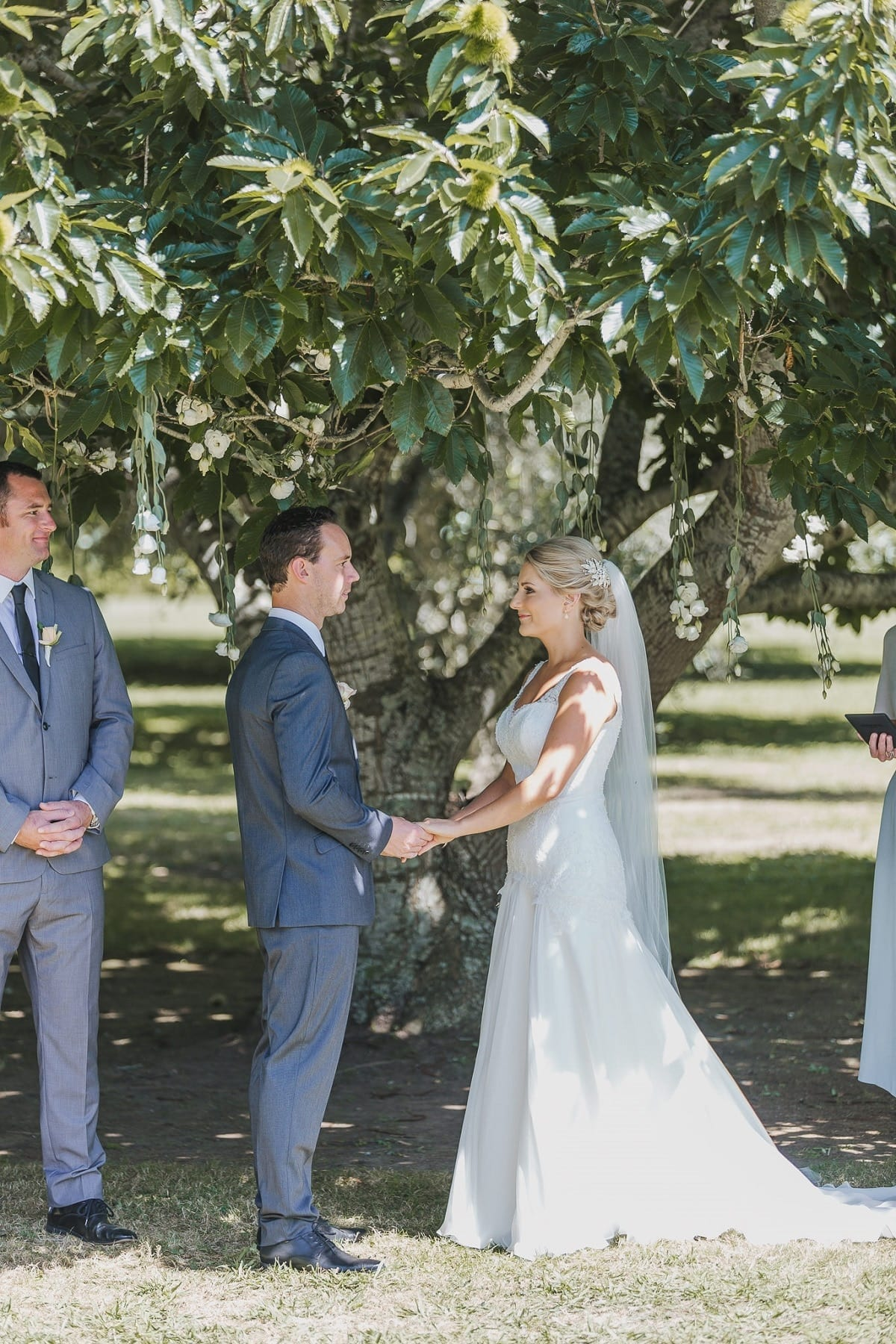 Real Weddings | Vinka Design | Real Brides Wearing Vinka Gowns | Sophie and Auldan outdoors under tree