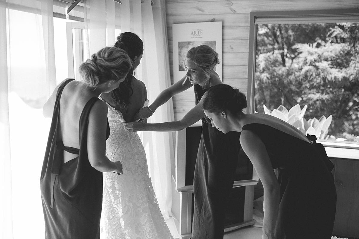 Real Weddings | Vinka Design | Real Brides Wearing Vinka Gowns | Clare and Mark - Clare getting ready with bridesmaids helping in black and white