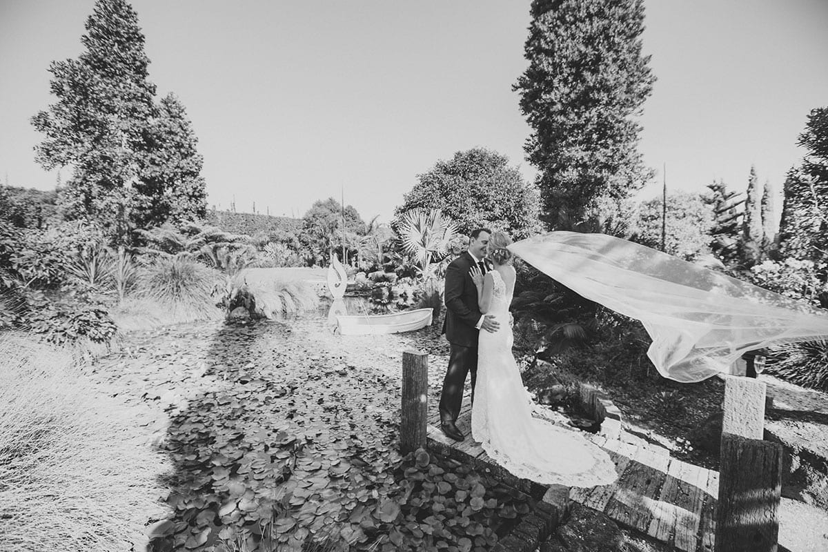 Real Weddings | Vinka Design | Real Brides Wearing Vinka Gowns | Angela and Tony outdoors next to pond kissing in black and white