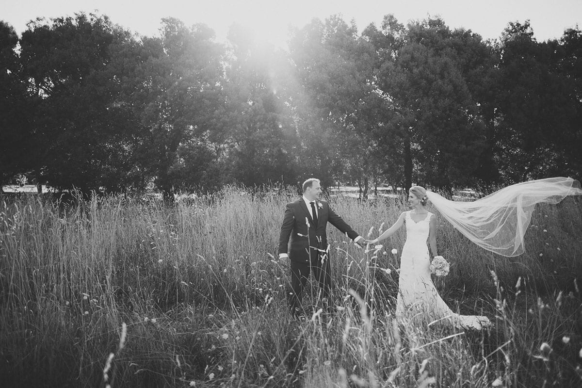 Real Weddings | Vinka Design | Real Brides Wearing Vinka Gowns | Angela and Tony in field holding hands with veil in breeze in black and white