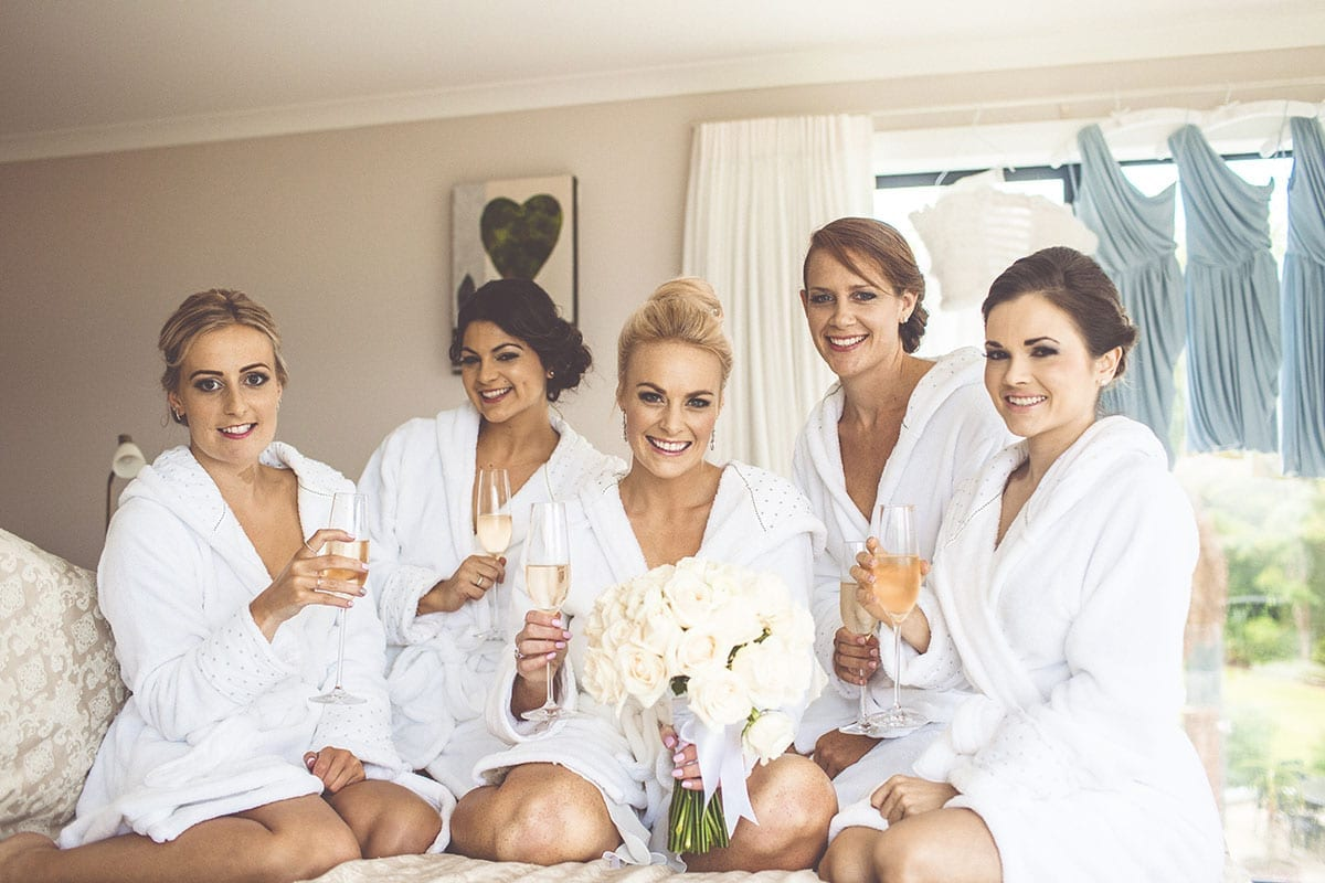 Real Weddings | Vinka Design | Real Brides Wearing Vinka Gowns | Kristen and Ben - Kristen getting ready with bridesmaids drinking champagne
