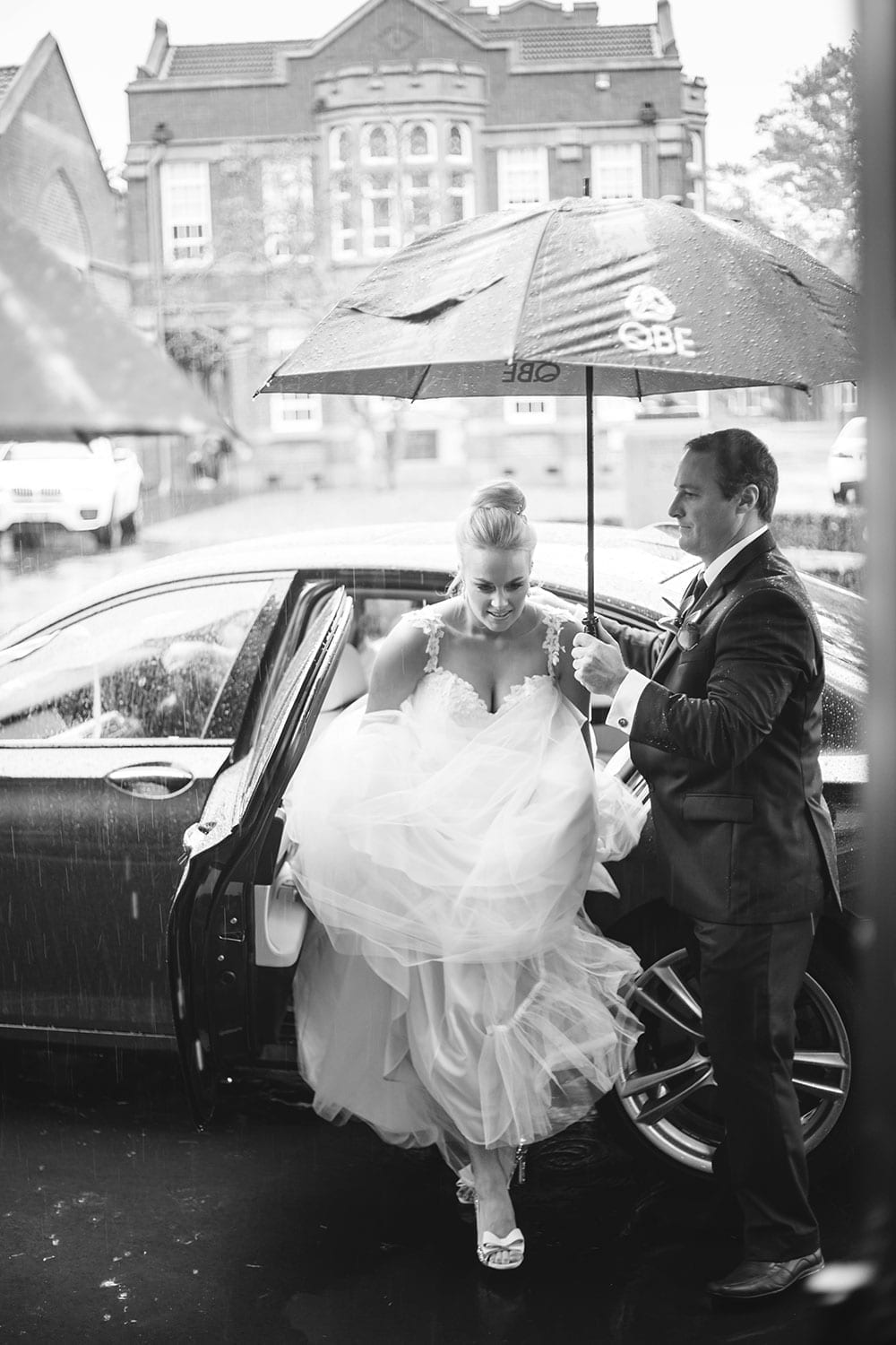 Real Weddings | Vinka Design | Real Brides Wearing Vinka Gowns | Kristen and Ben black and white getting out of car with umbrella