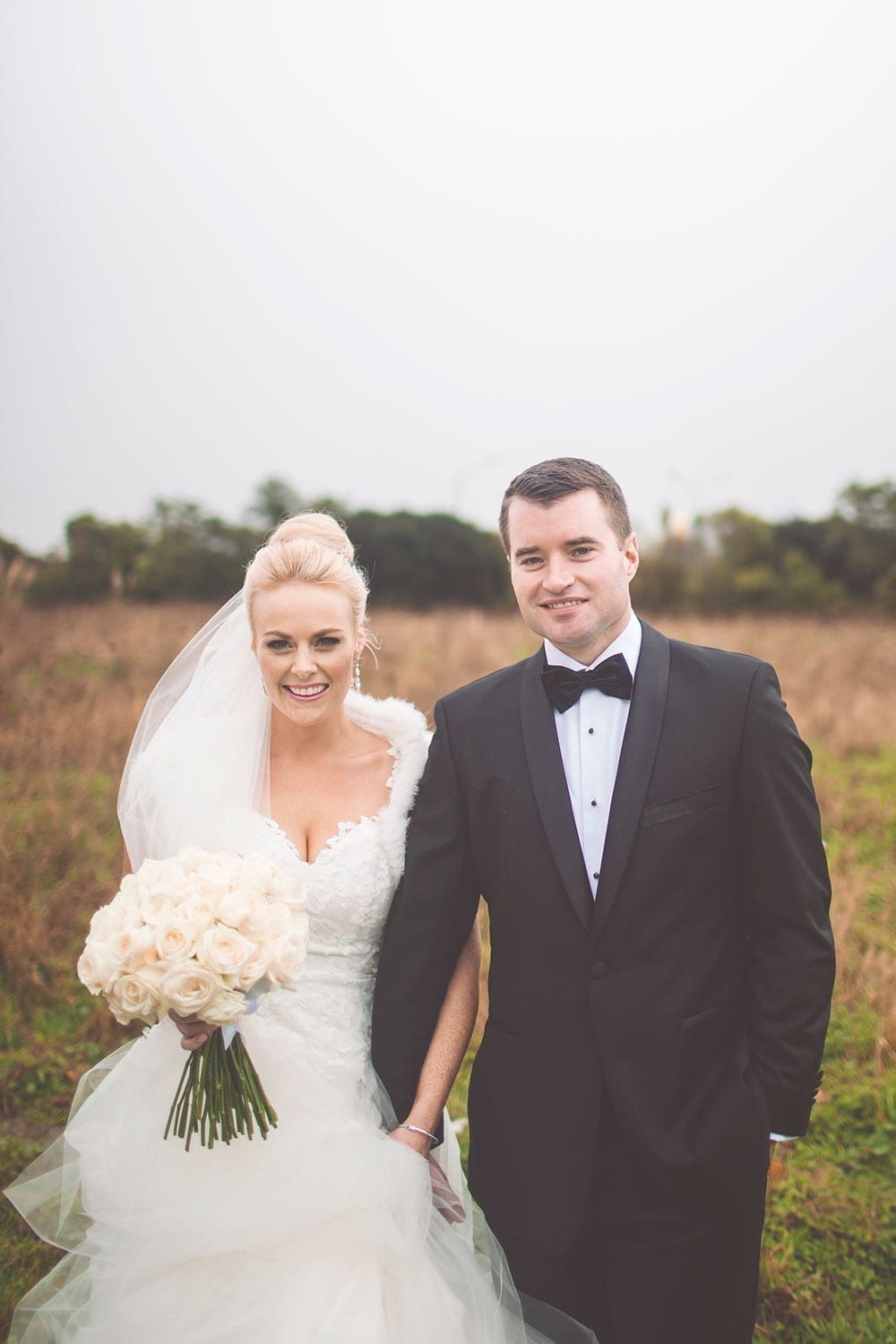 Real Weddings | Vinka Design | Real Brides Wearing Vinka Gowns | Kristen and Ben outdoors in field holding hands