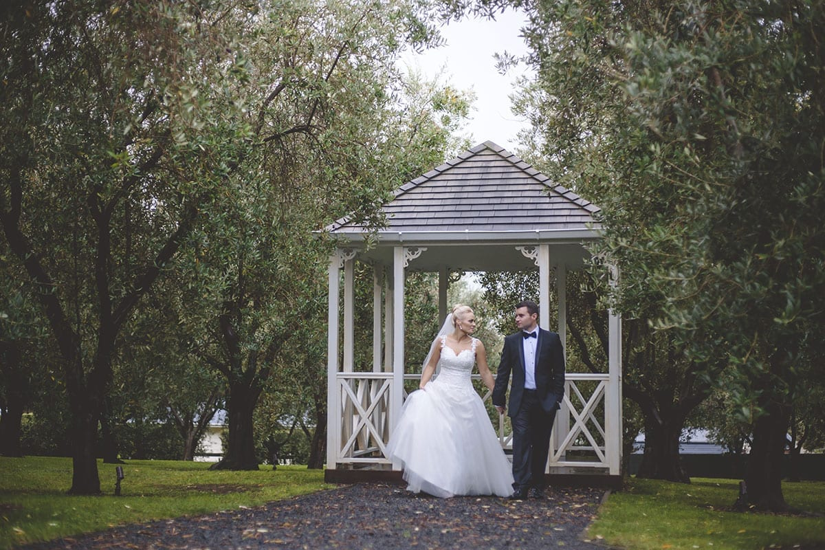 Real Weddings | Vinka Design | Real Brides Wearing Vinka Gowns | Kristen and Ben outdoors in front of wooden pagoda