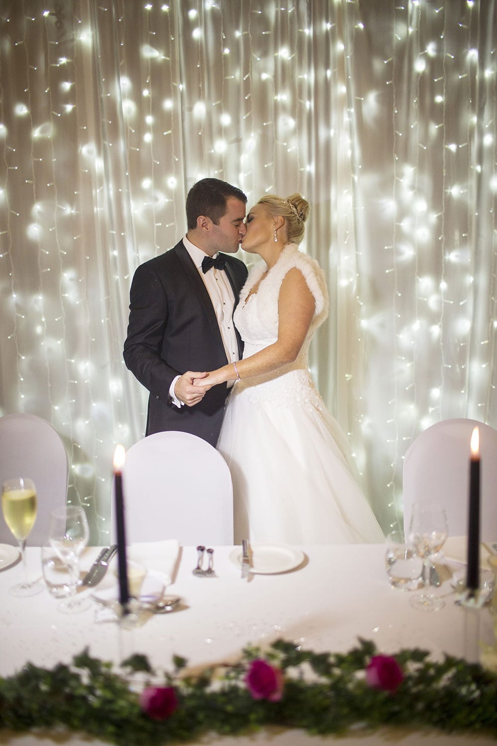 Real Weddings | Vinka Design | Real Brides Wearing Vinka Gowns | Kristen and Ben kissing at wedding reception table