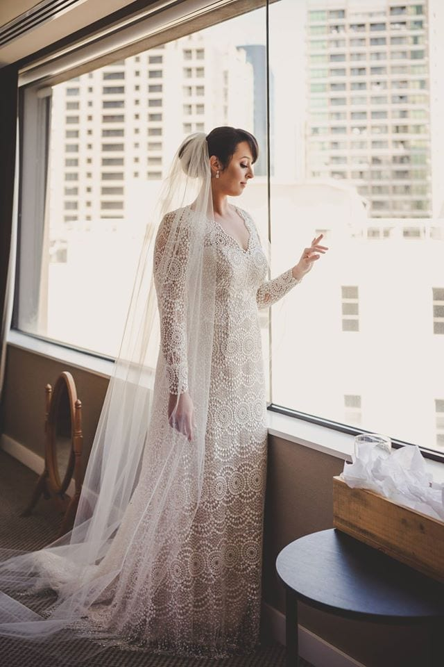 Real Weddings | Vinka Design | Real Brides Wearing Vinka Gowns | Jade portrait looking out of window highlighting full dress lace detail and veil