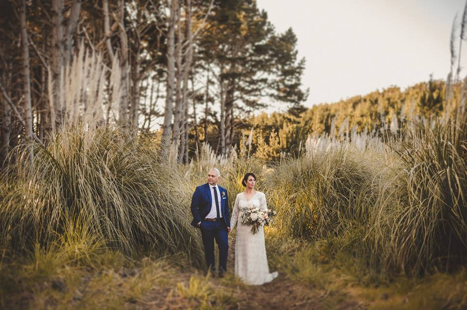 Real Weddings | Vinka Design | Real Brides Wearing Vinka Gowns | Jade and Brett walking through overgrowth in forest