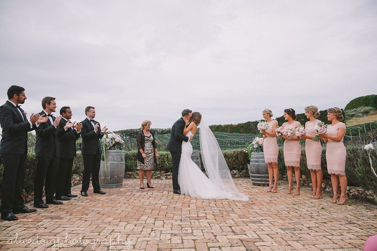 Real Weddings | Vinka Design | Real Brides Wearing Vinka Gowns | Gemma and Colin kissing with bridal party surrounding