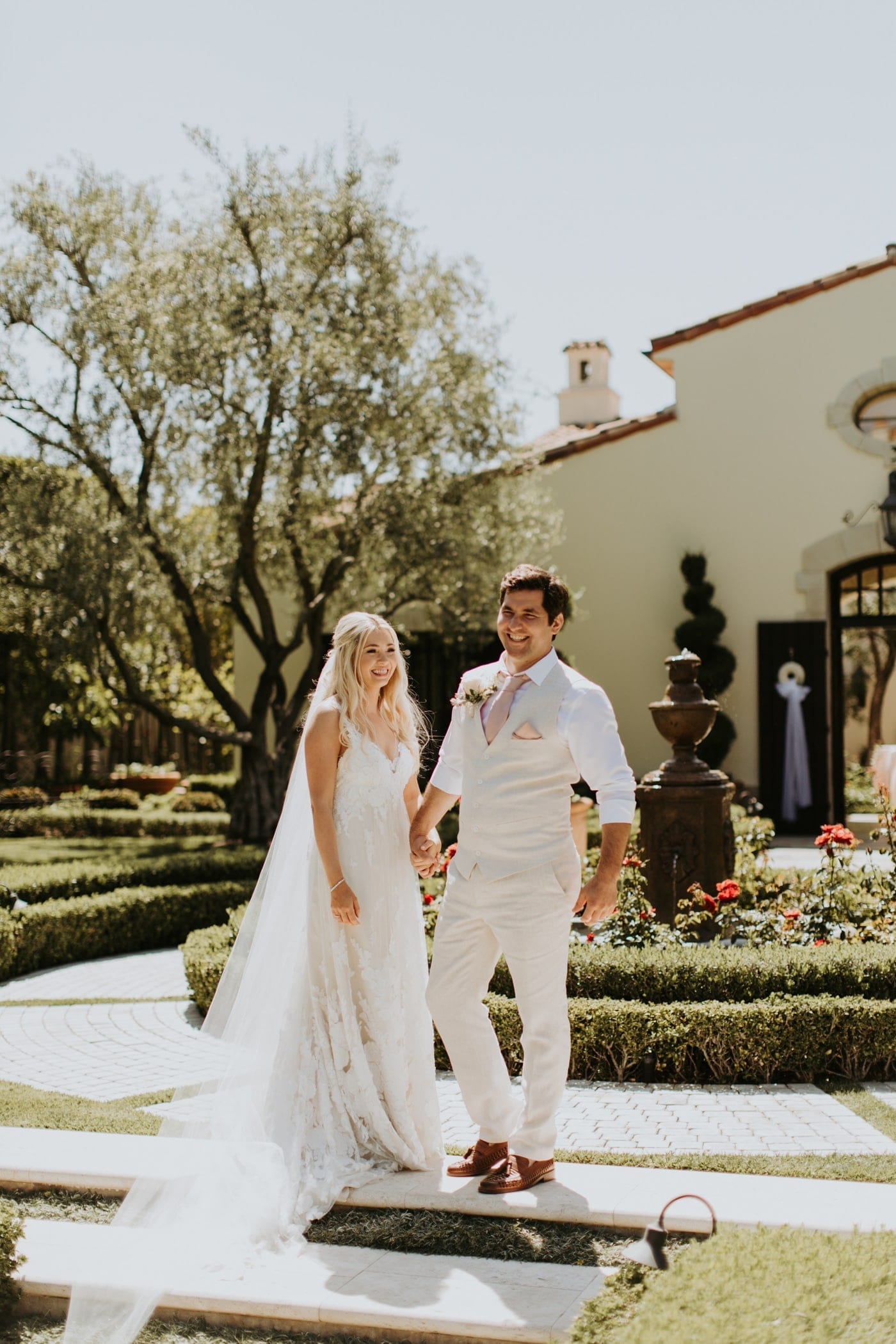Real Weddings | Vinka Design | Real Brides Wearing Vinka Gowns | Camille and Aaron in the Californian sun with dress and veil displayed smilin