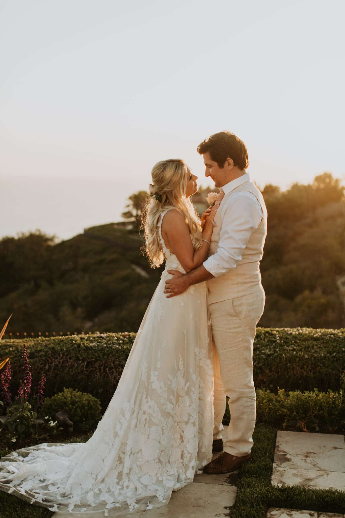 Real Weddings | Vinka Design | Real Brides Wearing Vinka Gowns | Camille and Aaron kissing in the California sun with the dress train lace detail shining