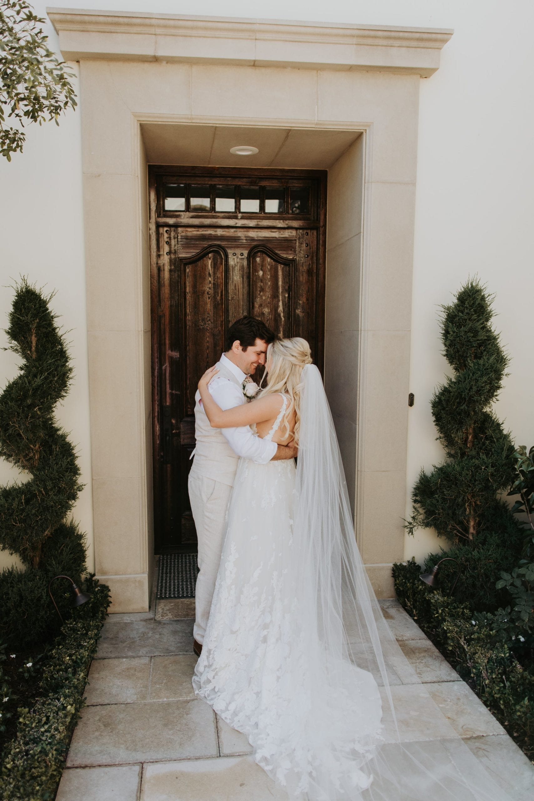 Real Weddings | Vinka Design | Real Brides Wearing Vinka Gowns | Camille and Aaron kissing in doorway dress flowing along ground