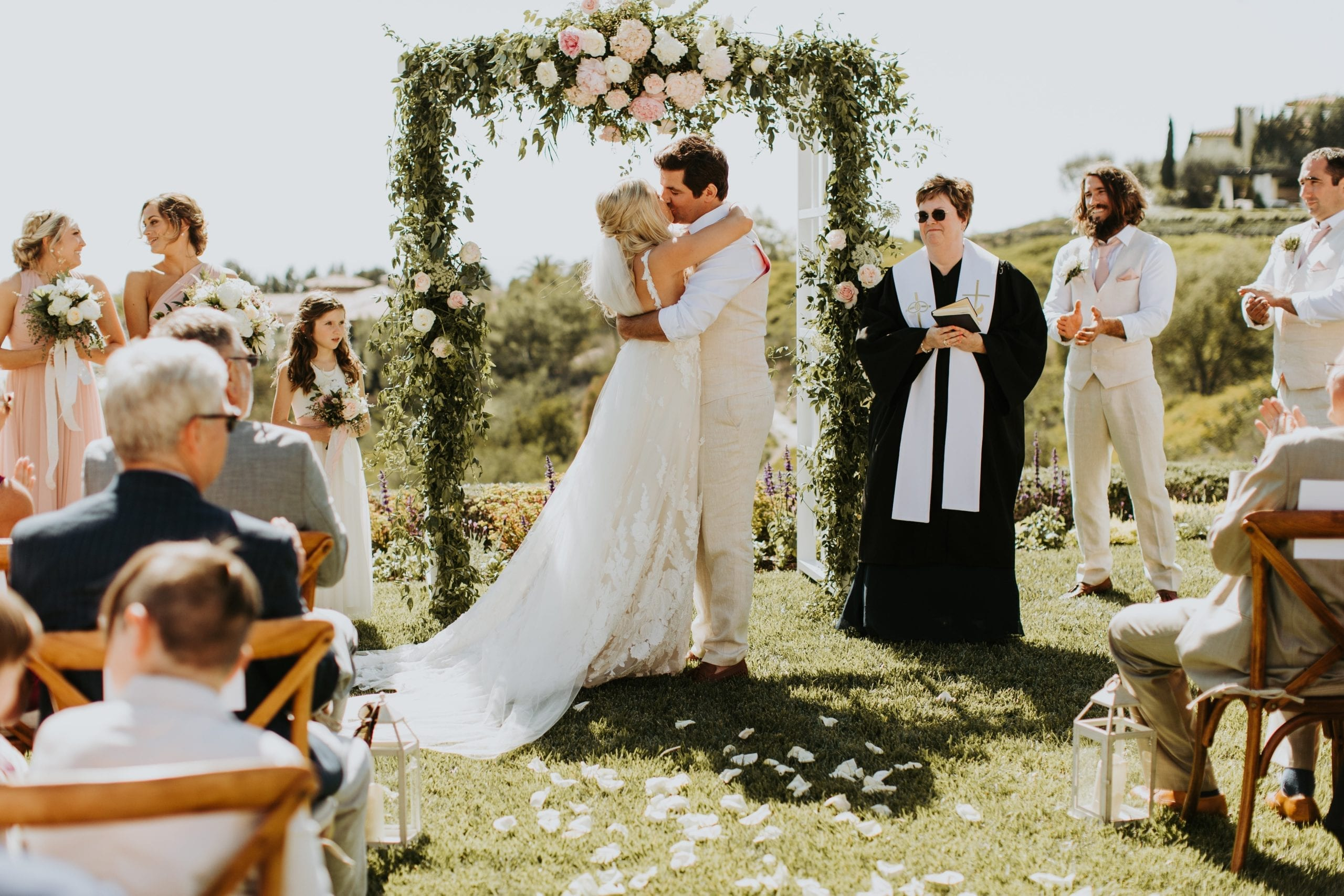 Real Weddings | Vinka Design | Real Brides Wearing Vinka Gowns | Camille and Aaron kissing in archway at ceremony