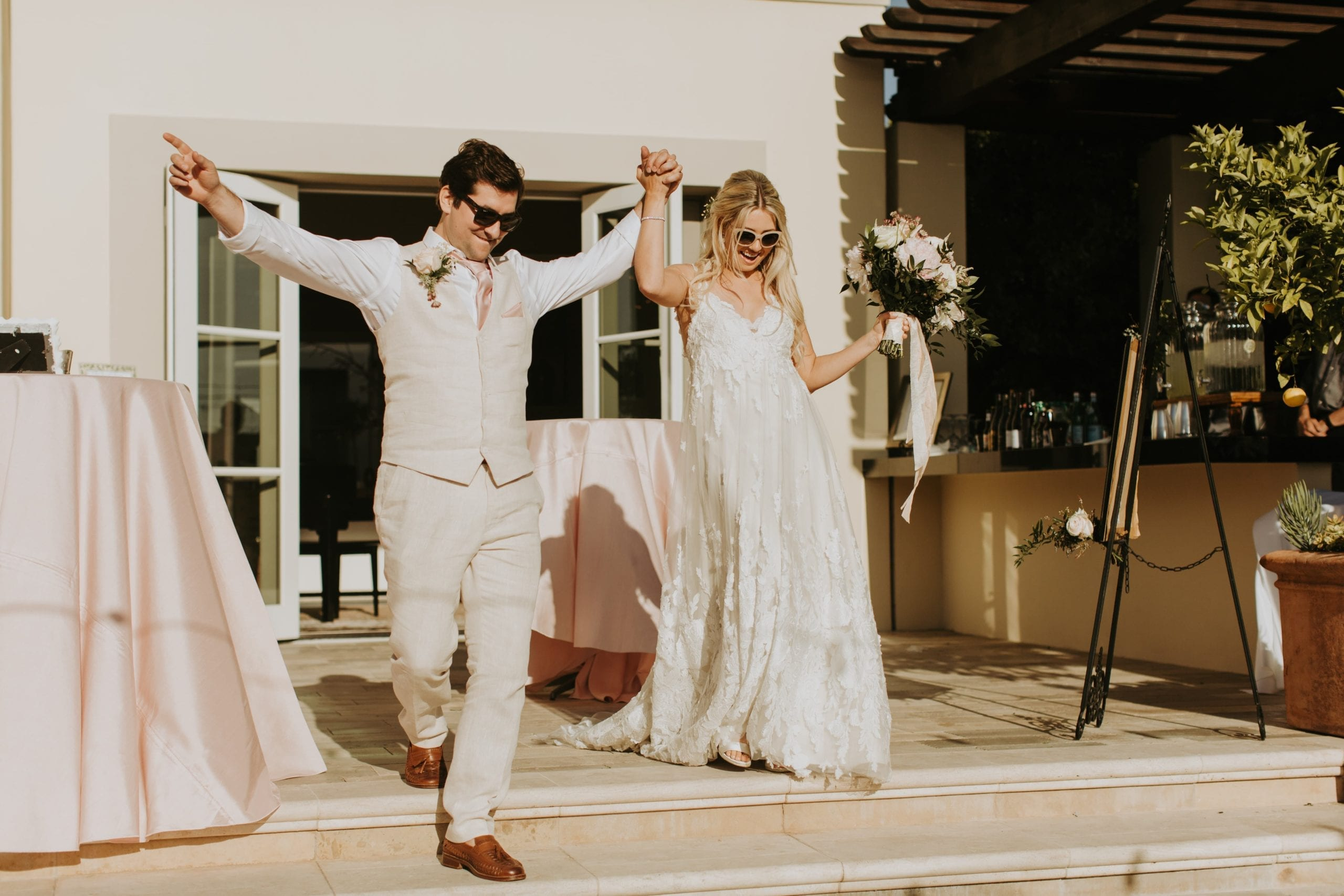 Real Weddings | Vinka Design | Real Brides Wearing Vinka Gowns | Camille and Aaron arms in the air coming down steps just married
