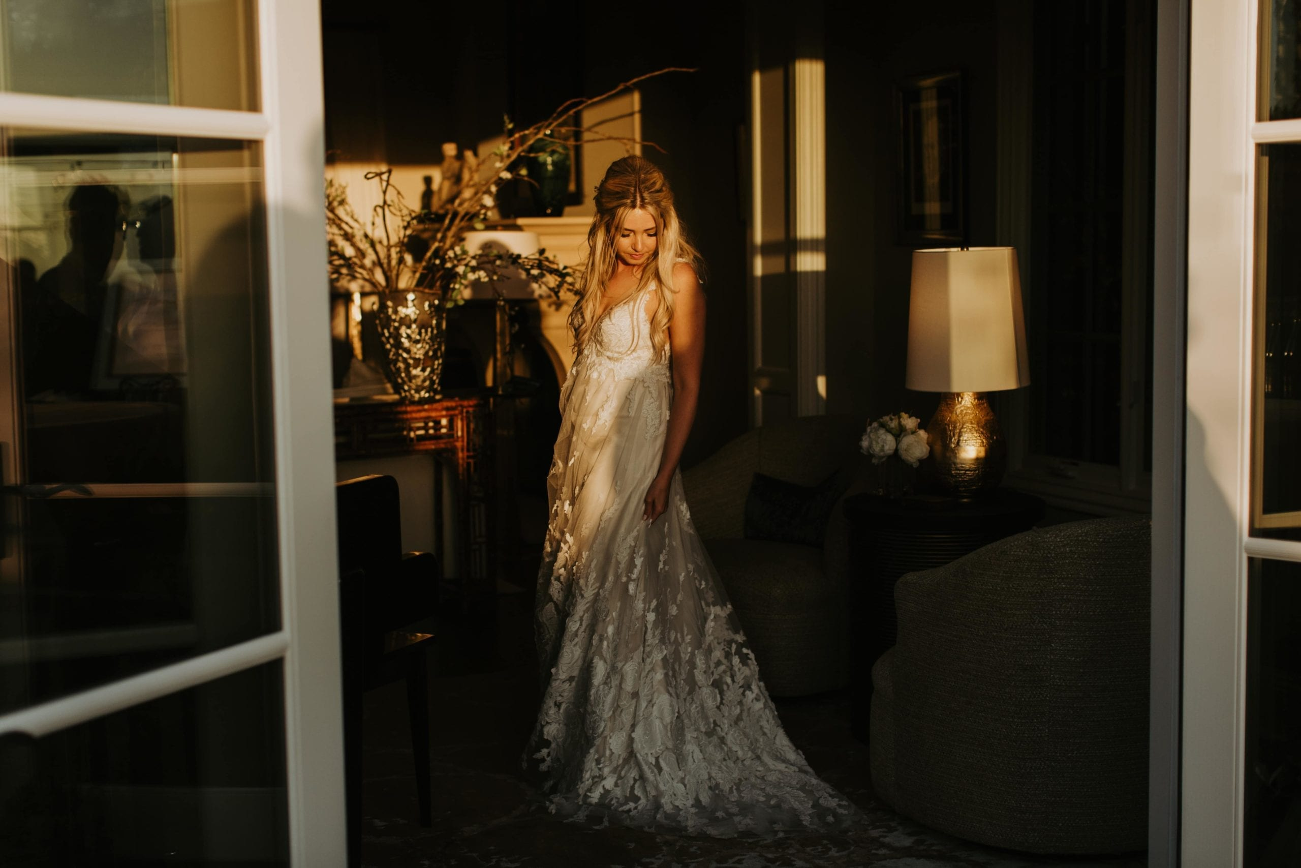 Real Weddings | Vinka Design | Real Brides Wearing Vinka Gowns | Camilla and Aaron - Camilla in doorway with beautiful bespoke wedding dress falling to her side