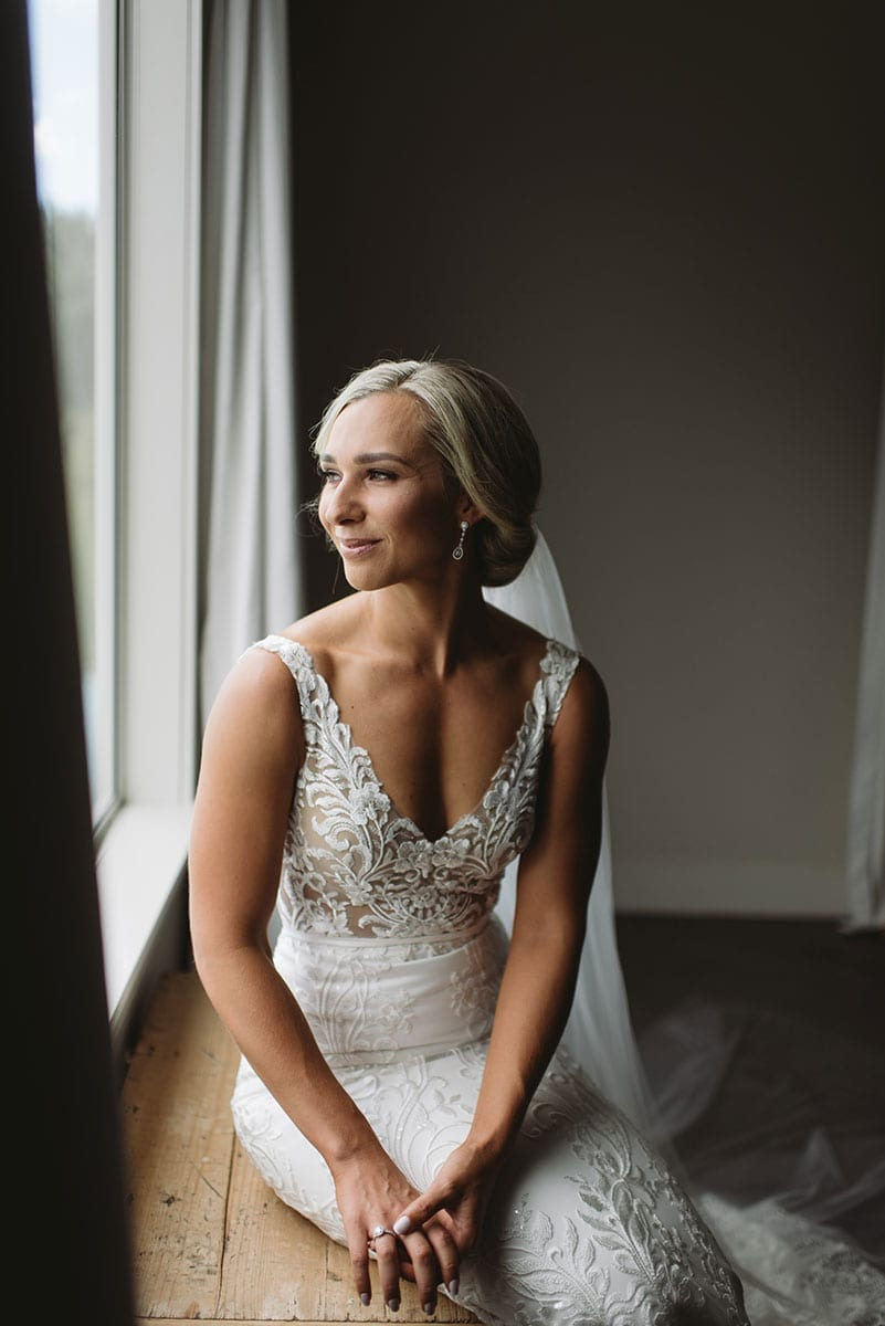 Real Weddings | Vinka Design | Real Brides Wearing Vinka Gowns | Nikki and Korey - Nikki seated looking out of window the light highlighting the lace detail