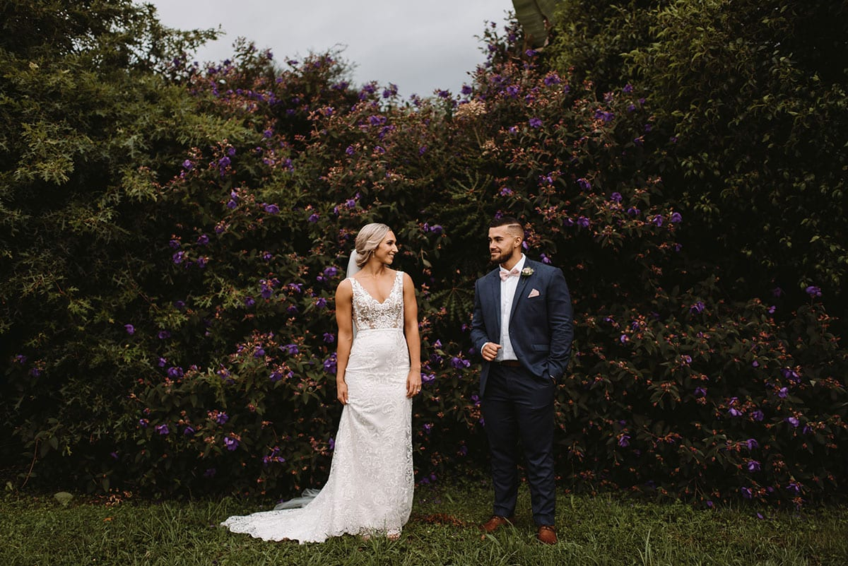 Real Weddings | Vinka Design | Real Brides Wearing Vinka Gowns | Nikki and Korey outdoors with forest backdrop showing full front of bespoke wedding gown with v neck detail