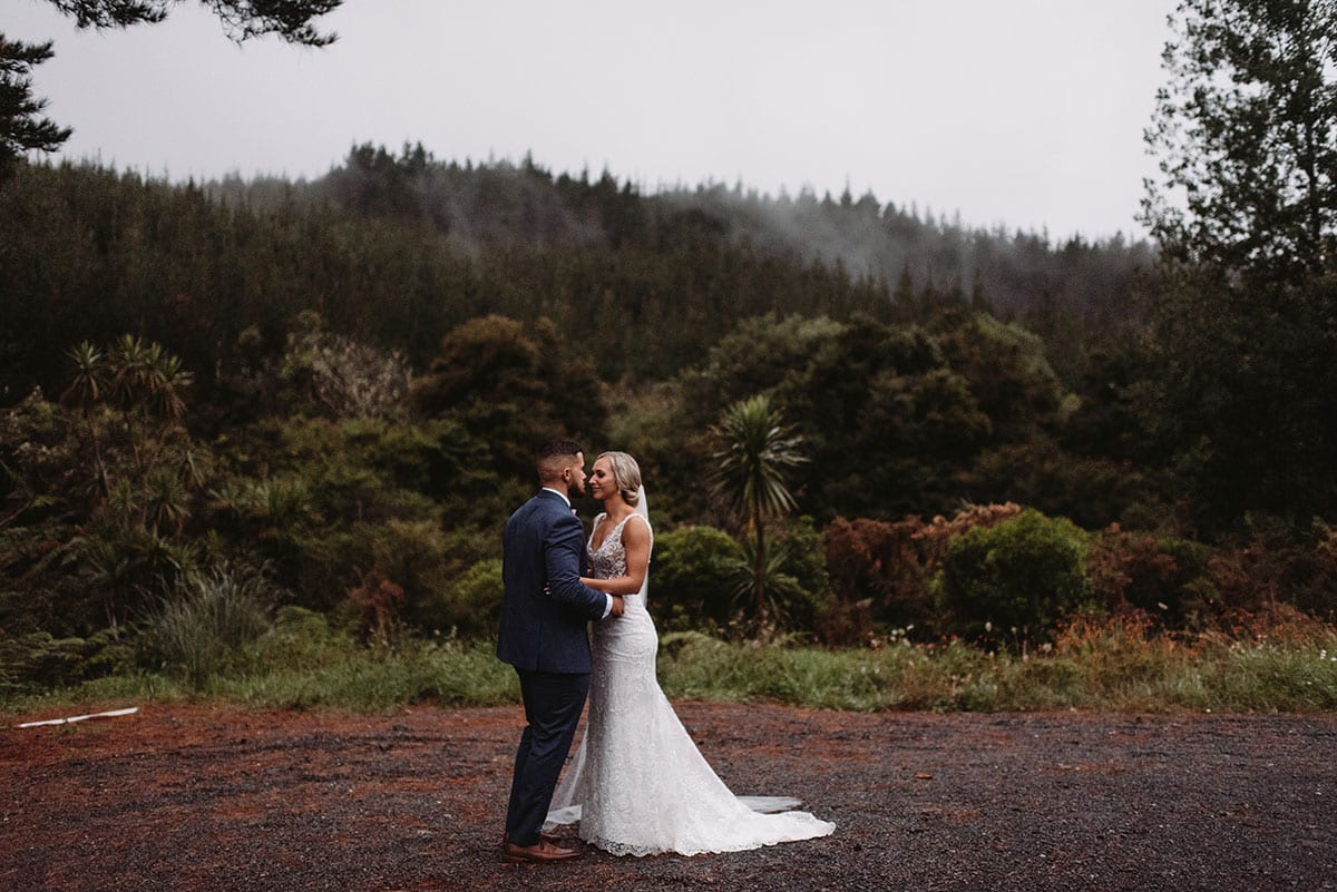 Real Weddings | Vinka Design | Real Brides Wearing Vinka Gowns | Nikki and Korey outdoors with forest backdrop