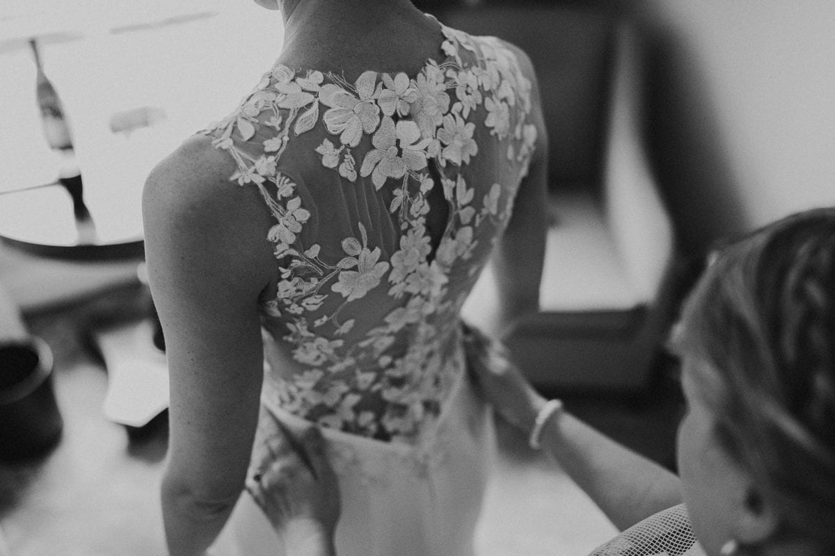 Real Weddings | Vinka Design | Real Brides Wearing Vinka Gowns | Paige and Ciaran - Paige getting ready close up of stunning sheer back of bespoke gown with lace floral detail