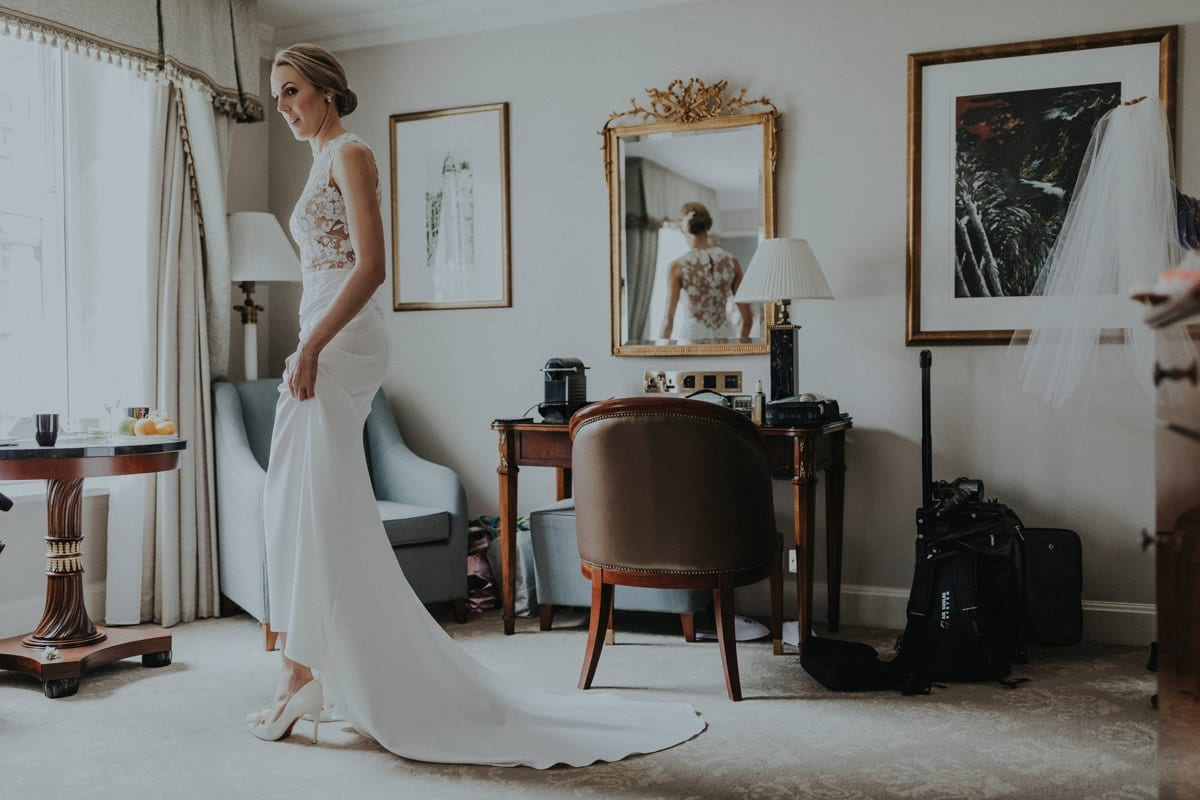 Real Weddings | Vinka Design | Real Brides Wearing Vinka Gowns | Paige and Ciaran - Paige getting ready putting on shoes with dress train flowing behind her