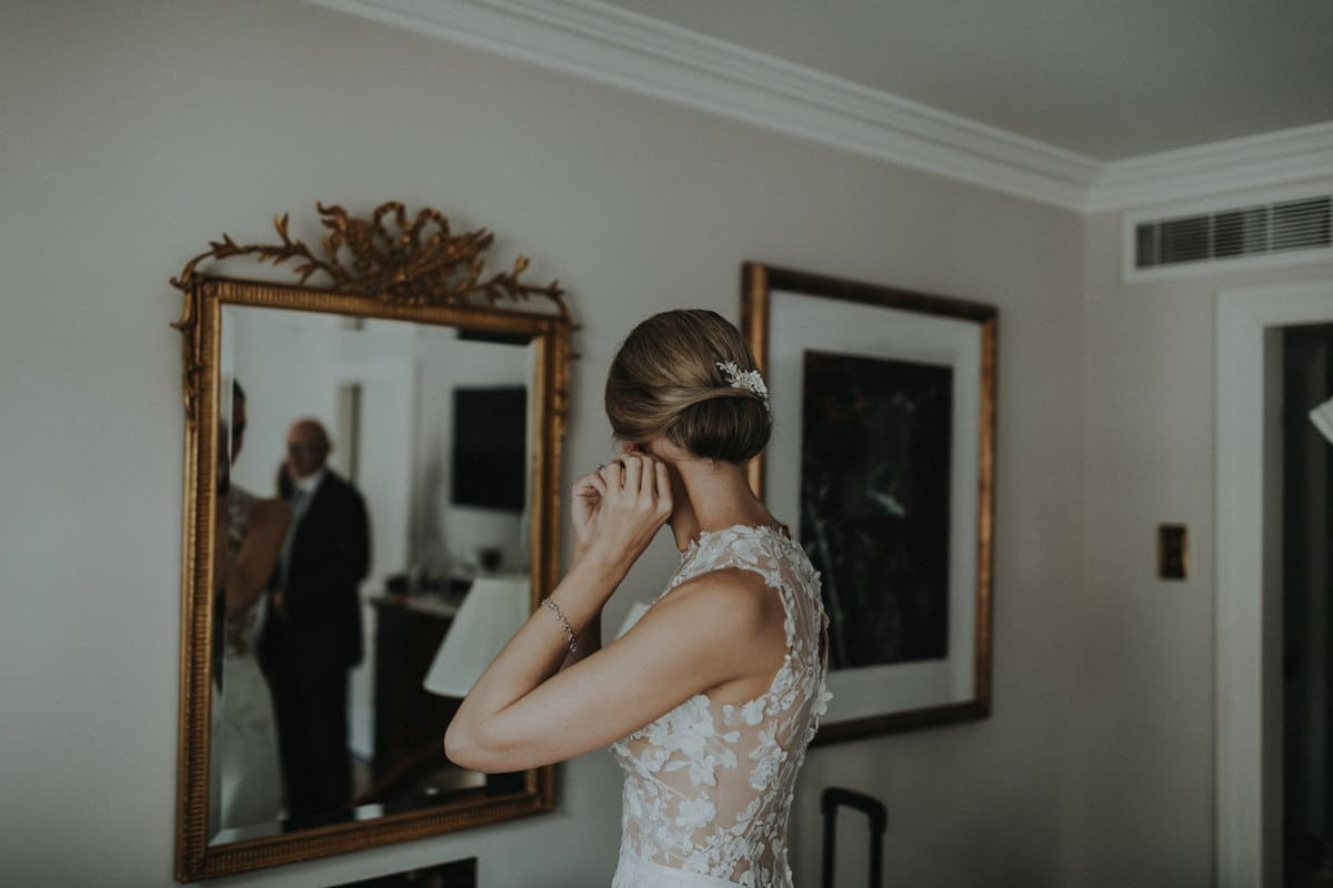 Real Weddings | Vinka Design | Real Brides Wearing Vinka Gowns | Paige and Ciaran - Paige getting ready putting in earrings