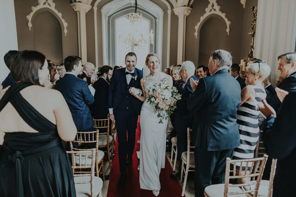 Real Weddings | Vinka Design | Real Brides Wearing Vinka Gowns | Paige and Ciaran walking from ceremony with sleek skirt of bespoke gown highlighted