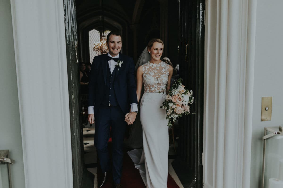 Real Weddings | Vinka Design | Real Brides Wearing Vinka Gowns | Paige and Ciaran walking through doorway with beautiful lace bodice and sleek skirt of bespoke gown highlighted