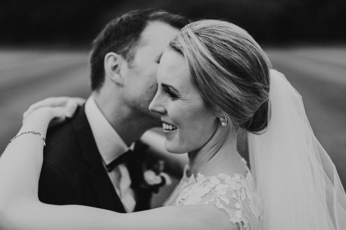 Real Weddings | Vinka Design | Real Brides Wearing Vinka Gowns | Paige and Ciaran close up of faces embracing in black and white